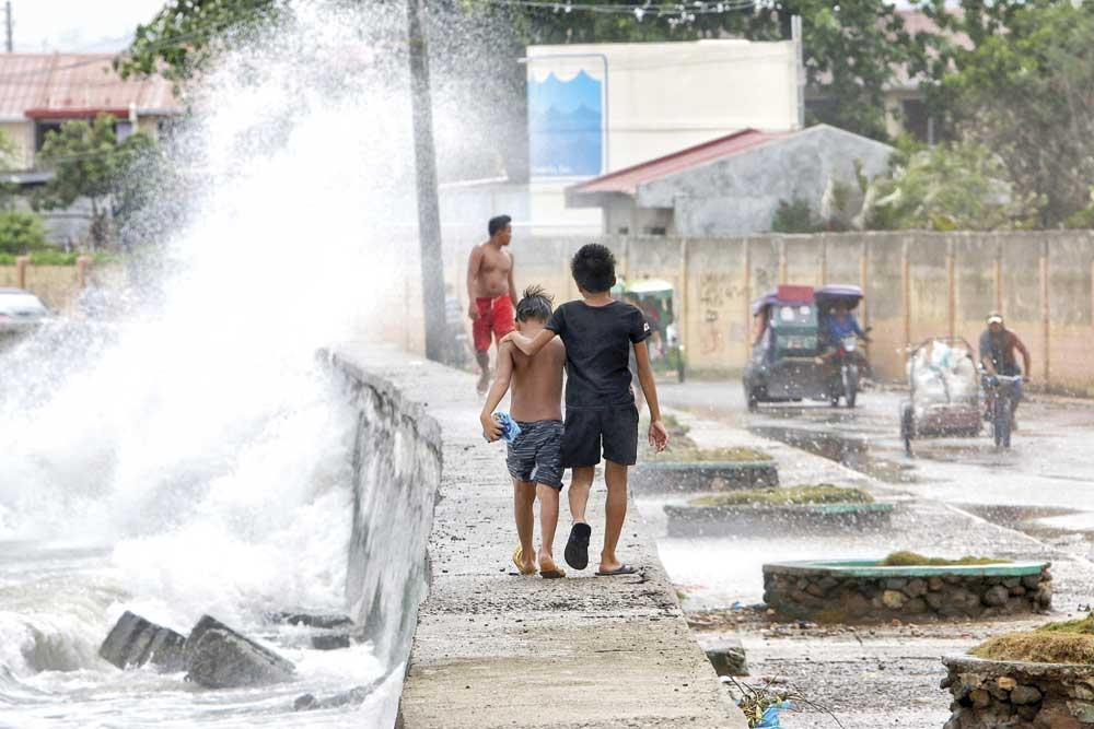 CALM AMID THE STORM. Two friends take a stroll on the seawall in Sitio Litmon, Barangay Poblacion, Talisay City, unmindful of the several meters high waves that lash at the coast as a result of typhoon Ompong. (SunStar foto / Alex Badayos)