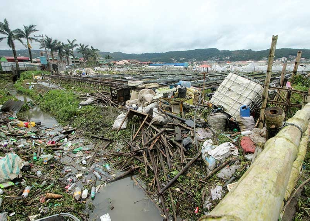 BENGUET. Debris from shattered stalls, plant covers and plastic wastes are scattered along a canal at the La Trinidad strawberry farm. The farm was flooded when typhoon Ompong struck. Farmers said it was the worst storm they have experienced. (Photo by Jean Nicole Cortes)
