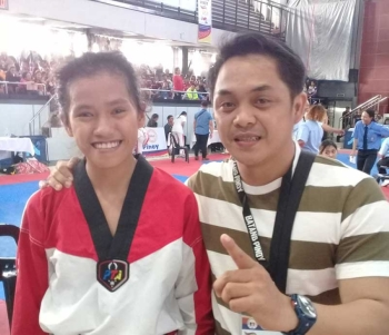 BAGUIO. 13-year-old Charisse Esclamado (with her coach Ben Ree Toledo) gives Cagayan de Oro's first gold medal after ruling the taekwondo cadet female LTM category in the 2017-2018 Batang Pinoy National Championships on Monday at the University of Baguio gym. (Jaime A. Frias II)