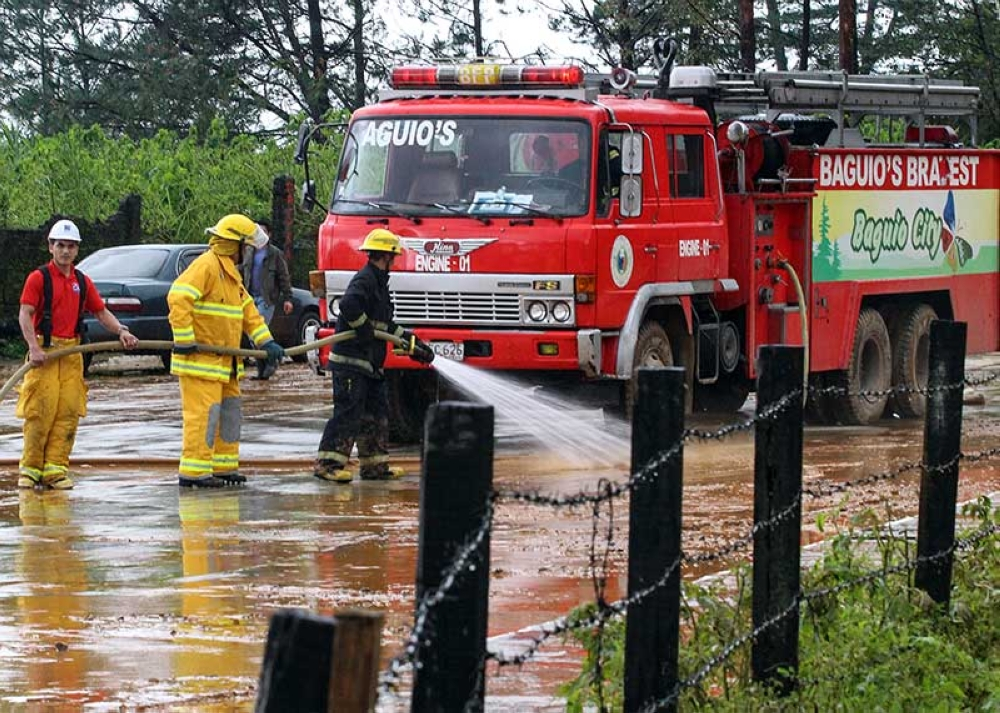 BAGUIO. A group of firemen sprays water on the muddy roads at Loakan near the airport to prevent vehicles and passers from slipping. Meanwhile, search and rescue operations are still ongoing near the airport. (Photo by Jean Nicole Cortes)