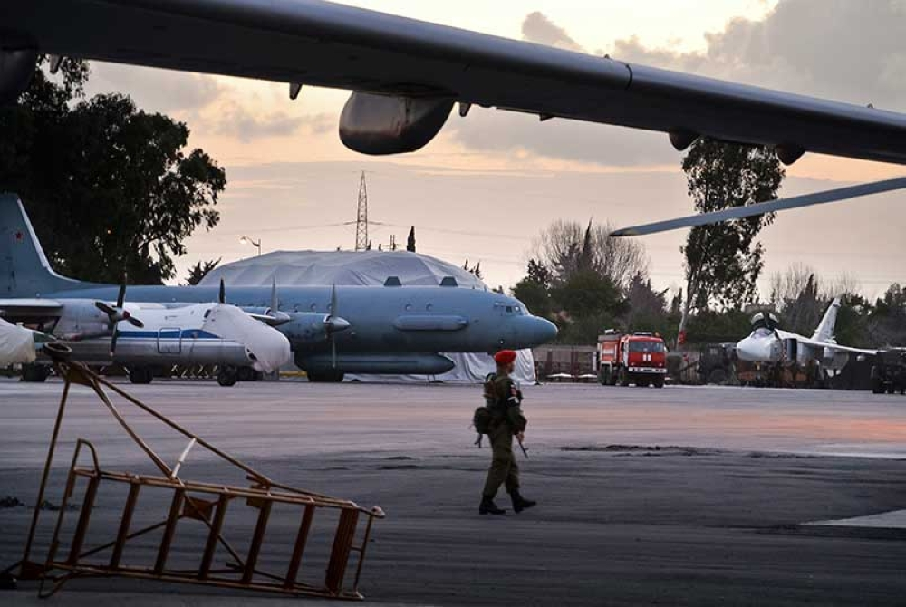 SYRIA. In this photo taken on Friday, March 4, 2016, A Russian military police officer stands guard at the Russian air base in Hemeimeem, Syria, with an Il-20 electronic intelligence plane of the Russian air force is in the background. An Il-20 aircraft was shot down Tuesday, Sept. 18, 2018 by a Syrian missile over the Mediterranean Sea, killing all 15 people on board, as the Syrian military fired on Israeli fighter jets attacking targets in northwestern Syria. (AP)