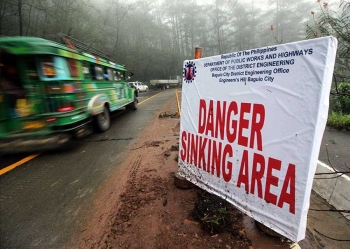 BAGUIO. A warning sign is posted along a sinking road at South Drive Baguio City. Motorists need to take precaution in traversing the roads in the city after several landslides occured brought about by Typhoon Ompong. (Photo by Jean Nicole Cortes)