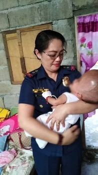 ONE GOOD ACT. Police Senior Inspector Jacqueline Gahid carries the 4-month old baby girl with hydrocephalus during her personal visit at her house to extend financial and in-kind assistance. (Contributed photo)