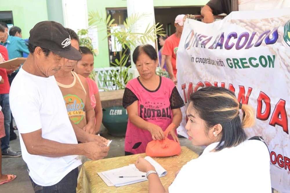 "Residents of Barangay Singcang-Airport in Bacolod City buy P27 per kilogram government rice through the ""tagpuan"" launched by the National Food Authority in Negros Occidental in front of the barangay hall yesterday. (Contributed photo)"