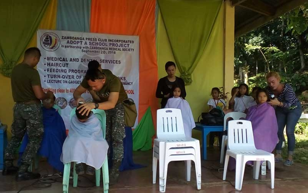 ZAMBOANGA. Marine Battalion Landing Team-11 personnel and Rain's Beauty Salon and Barbershop beauticians render free haircut during the community outreach program on Thursday, September 20, of the Zamboanga Press Club, Inc. in Guisao Elementary School. (Bong Garcia)