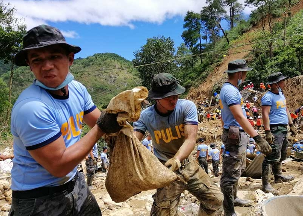 BAGUIO. Policemen pass on sacks of mud at ground zero of level 070 in Ucab, Itogon, Benguet as search and retrieval operations is ongoing for the victims of landslides. (Photo by Jean Nicole Cortes)