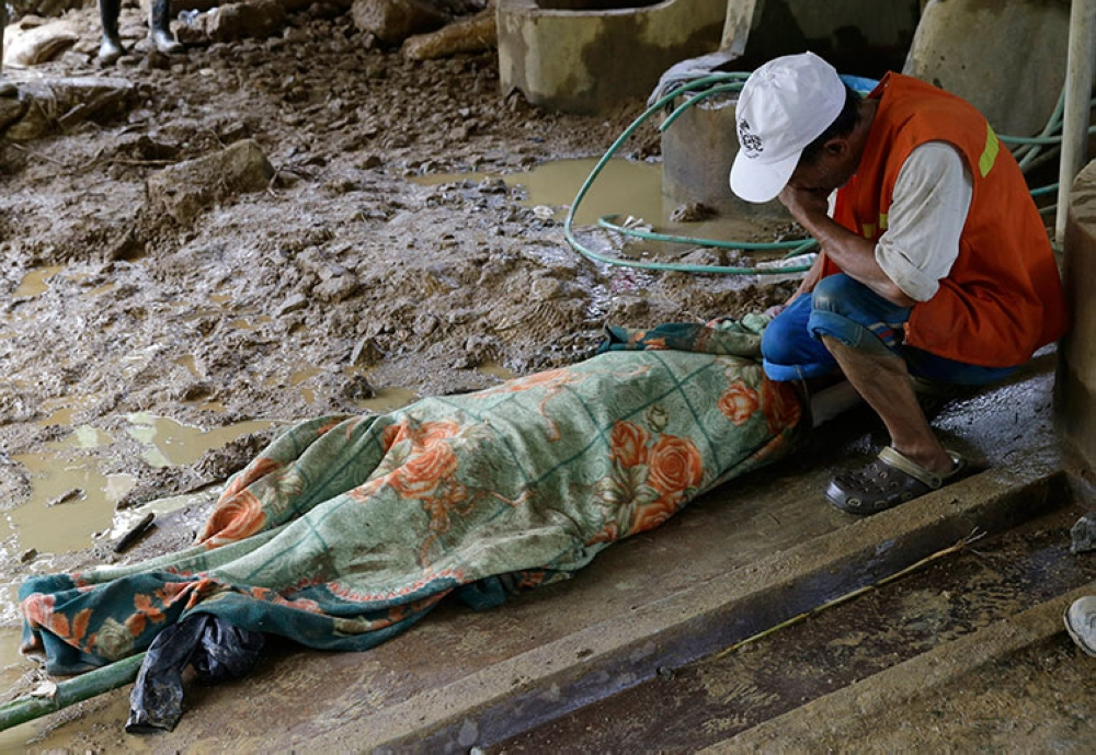 BENGUET. In this September 17, 2018, file photo, Pio Badangayon cries while seeing the body of her son-in-law Edwin Banawol after it was retrieved by rescuers at the site where victims are believed to have been buried by a landslide after Typhoon Ompong lashed Itogon, Benguet (AP)