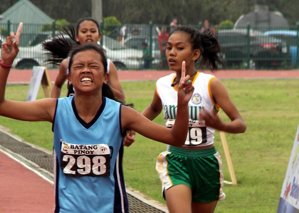 DAVAO. Ira Mae Gali, a Grade 9 student of Baguio City National High School flashes a victory sign after winning the gold in the 3,000 meter run against favorite and Palarong Pambansa gold medalists Leslie de Lima of Camarines Sur and Magvrylle Matchino of Laguna Province. Gali also bagged the gold medal earlier in the 800 meter run and a bronze in the 1,500 meter run. (Photo by Bong Cayabyab)