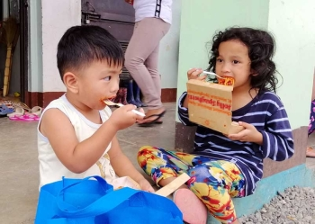 BAGUIO. Two kids at the evacuation center in Ucab, Itogon partake of food donated by volunteers as retrieval operations continue at the landslide-struck level 070. (Photo by Jean Nicole Cortes)