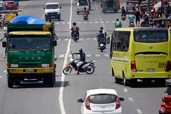 DAVAO. There are still a number of traffic violators in Davao City such as this motorcycle driver, who does not wear a helmet amidst huge trucks, driving along Maharlika Street in Tibungco. (Si Filemon)