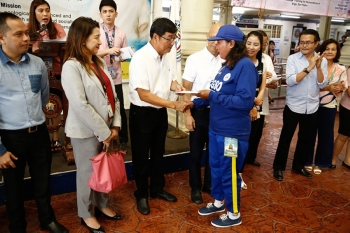 PAMPANGA. Mayor Edwin Santiago hand over to a city government employee her health card during the recent distribution at city hall. (Photo by CSF-CIO)
