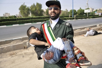 TEHRAN. In this photo provided by the Iranian Students' News Agency, ISNA, a Revolutionary Guard member carries a wounded boy after a shooting during a military parade marking the 38th anniversary of Iraq's 1980 invasion of Iran, in the southwestern city of Ahvaz, Iran, Saturday, September 22, 2018. Gunmen attacked the military parade, killing at least eight members of the elite Revolutionary Guard and wounding 20 others, state media said. (AP photo)