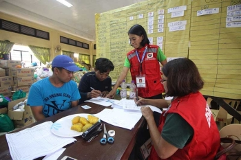 BAGUIO. DSWD workers assist two small-scale miners in filling up necessary documents to be able to receive the financial aid allocated for them. (Photo by Jean Nicole Cortes)