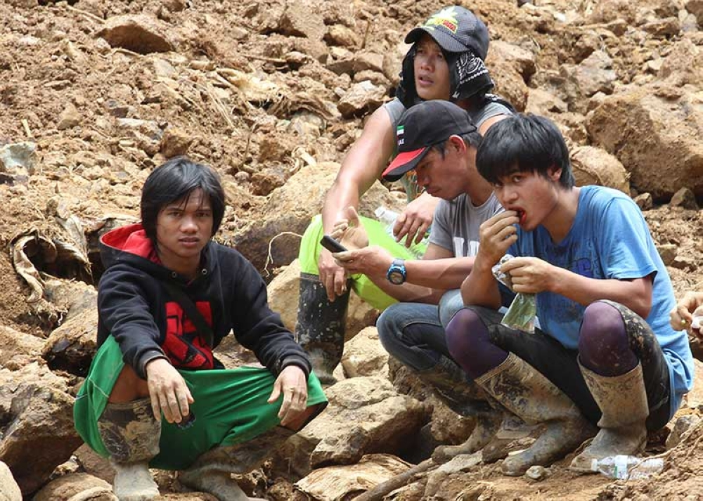 BAGUIO. Small-scale miners helping in the rescue operations at level 070 in Ucab, Itogon, Benguet get a fix of their betel nut chew while taking a break. (Photo by Jean Nicole Cortes)
