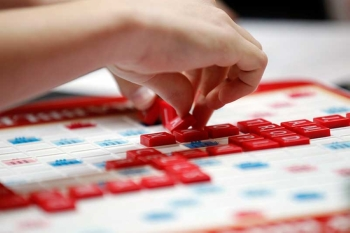 "This May 16, 2015 photo released by Hasbro shows a contestant competing in the first round of the 2015 North American School Scrabble Championship at Hasbro headquarters in Pawtucket, R.I. Merriam-Webster released the sixth edition of ""The Official Scrabble Players Dictionary"" early Monday with more than 300 additions. (Hasbro via AP)"