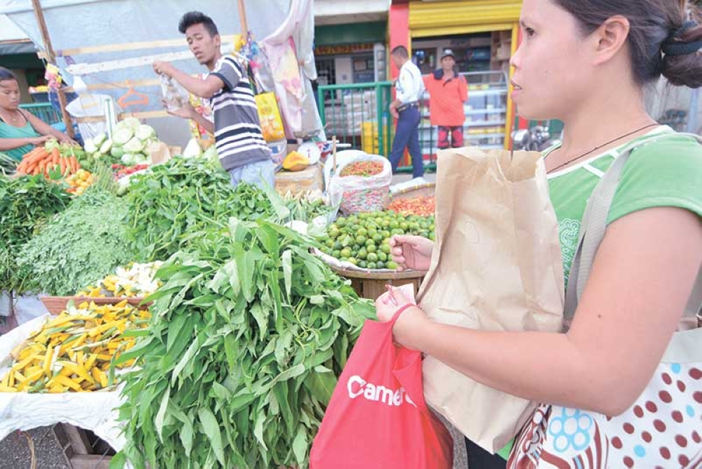 MARKET DAY. A woman passes by a display of vegetables at a roadside in Mandaue City. (SunStar file photo)