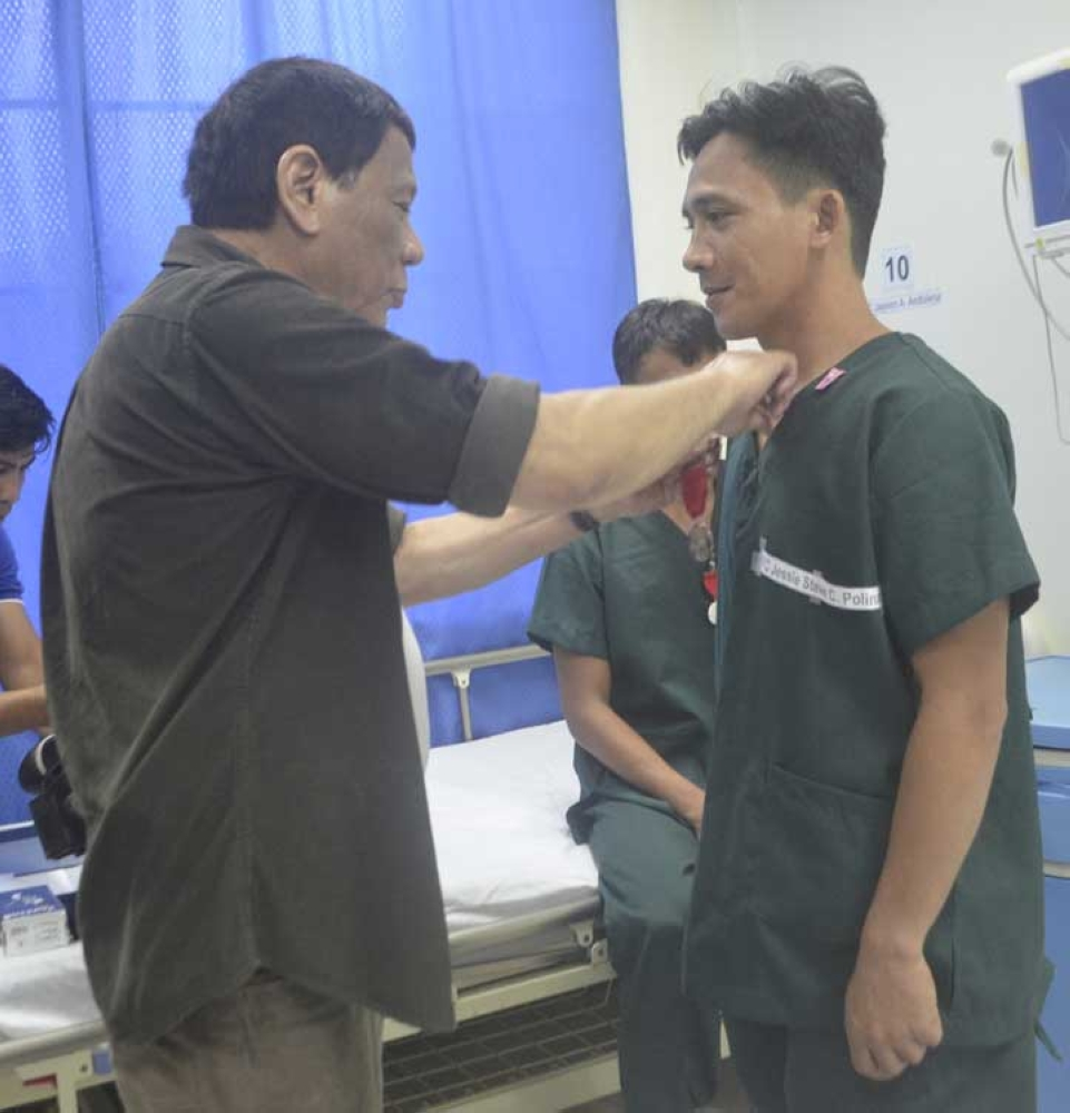ZAMBOANGA. Westmincom photo handout shows President Rodrigo Duterte pins medal to one of the soldiers, who were wounded in a clash against 100 Abu Sayyaf bandits on September 14 in Patikul, Sulu. The President on Monday, September 24, visited the troops of the Joint Task Force Sulu. (Bong Garcia)