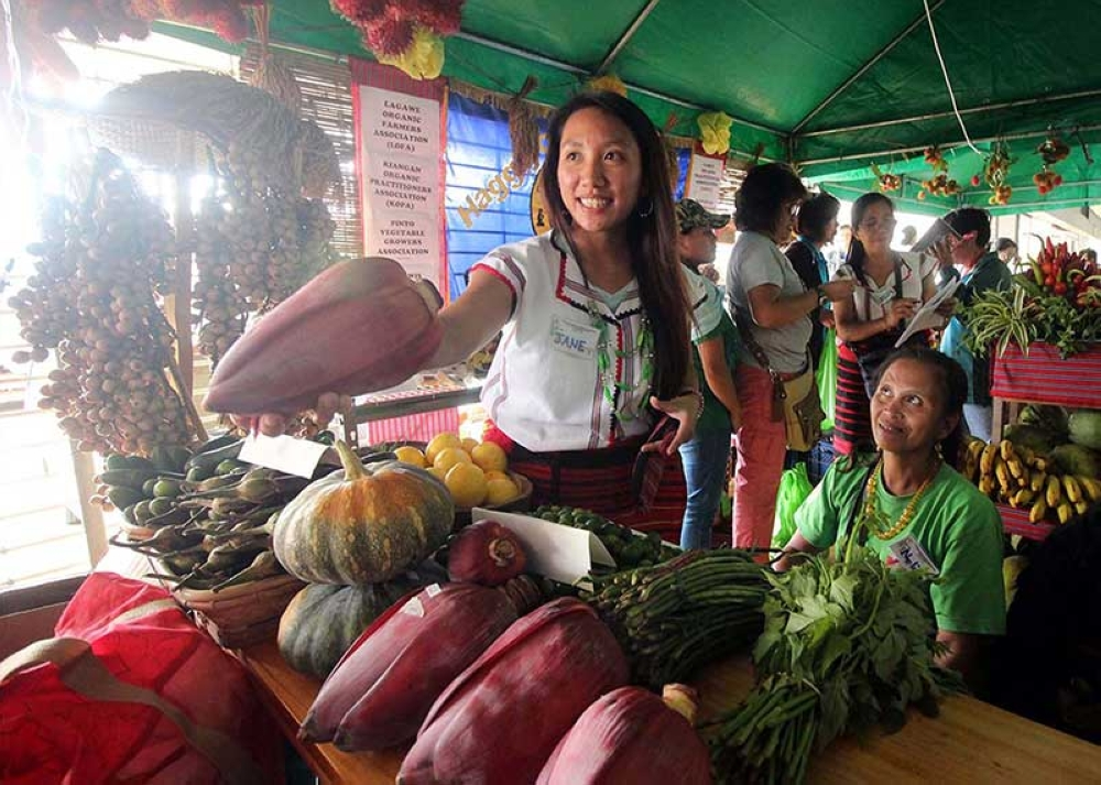 BAGUIO. A seller clad in her Igorot attire sells organic vegetables grown in Benguet. Prices of vegetables remain stable as supply continue to arrive in trading centers following the opening of major road networks in the region. (Photo by Jean Nicole Cortes)