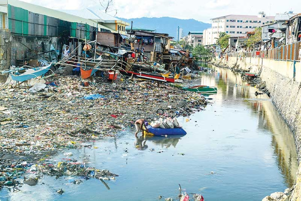 SHRINKING RIVER. The Guadalupe River exits through Barangays Pasil (left) and Ermita in Cebu City, much narrowed by the encroachment of houses and trash on its banks. Is it any wonder that when heavy rains come, the river overflows? (SunStar photo/Arni Aclao)