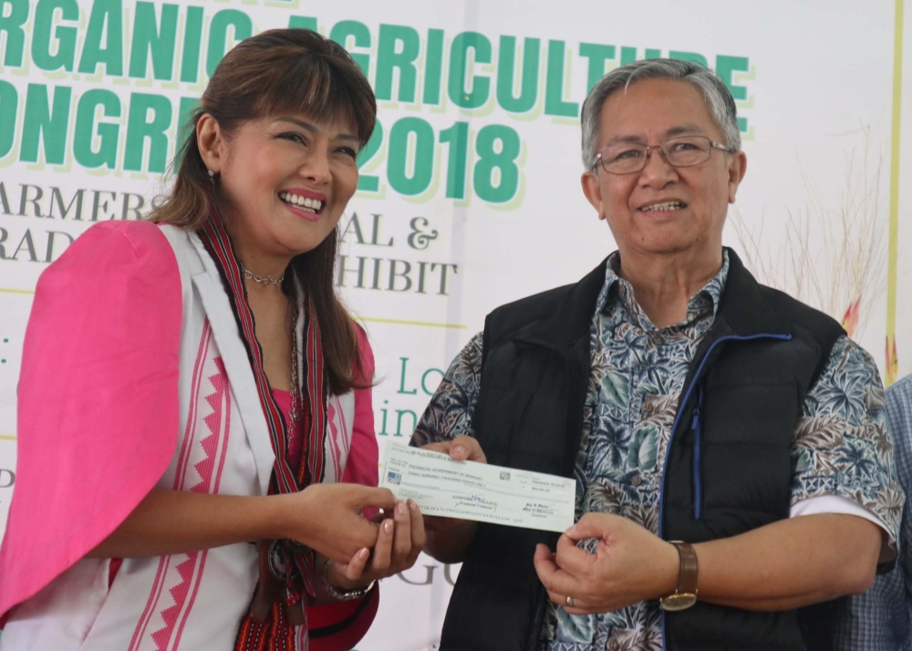 BAGUIO. Ilocos Governor Imee Marcos gives a check intended for Ompong victims to Benguet Governor Crescencio Pacalso during her visit at the 5th Agriculture Congress at the Benguet Agri-Pinoy Training Center on September 27.  (Contributed photo)