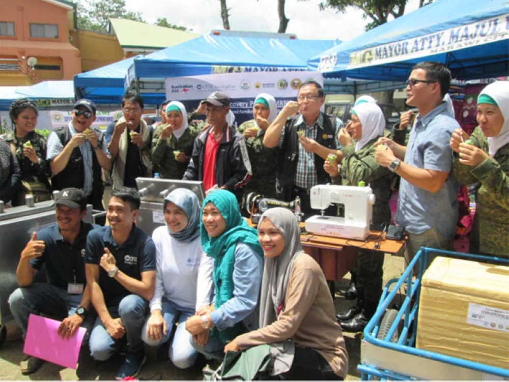 "MARAWI. Task Force Bangon Marawi Secretary Eduardo Del Rosario, with the ""Hijab Troopers,"" eat ice cream sold by one of the evacuees supported by Community and Family Services International (CFSI) during the second Kawiyagan. (Photo by Riz P. Sunio)"