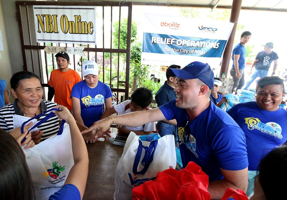 HELPING HAND. Veco Kaibigans brought a smile to one of the evacuees at the Enan Chiong Activity Center as they distributed relief packs to the landslide victims in the City of Naga last Sept. 22. (Contributed foto)