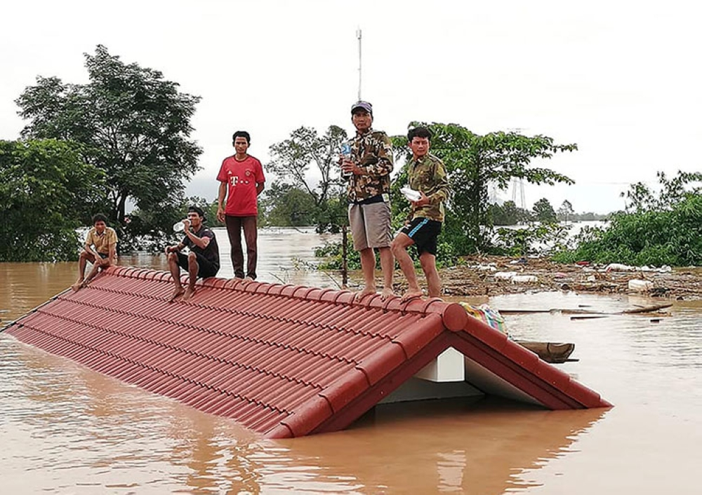 LAOS. In this July 24, 2018, file photo, villagers take refuge on a rooftop above flood waters from a collapsed dam in the Attapeu district of southeastern Laos. (AP)