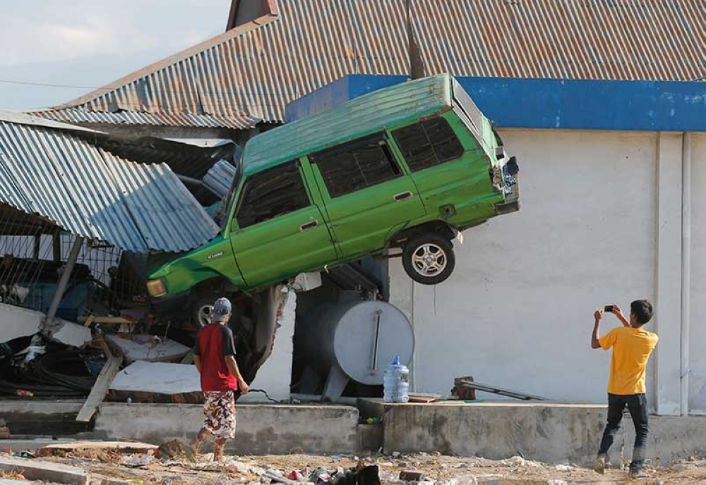 INDONESIA. A man takes a photo of a car lifted into the air with his mobile phone following a massive earthquake and tsunami at Talise beach in Palu, Central Sulawesi, Indonesia, Monday, Oct. 1, 2018. (AP)