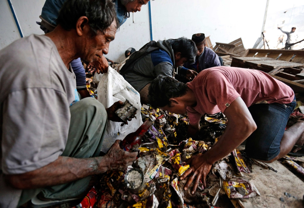 INDONESIA. Men dig through sodden piles of food inside an abandoned warehouse following an earthquake and tsunami in Palu, Central Sulawesi, Indonesia Indonesia, Wednesday, Oct. 3, 2018. (AP)
