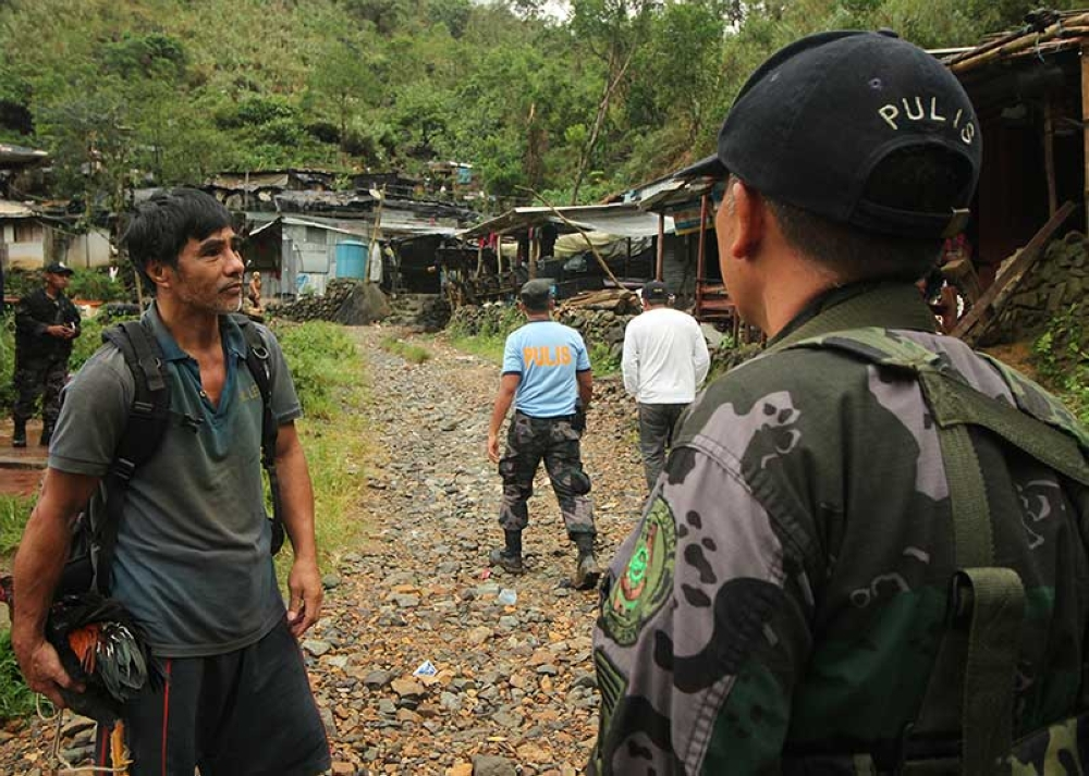 BAGUIO. Police, DENR and barangay officials visit small scale mining communities in Itogon, Benguet to warn them of the imminent danger if they stay in their shanties. Authorities are also implementing the closure of small scale mining in the area. (Photo by Jean Nicole Cortes)