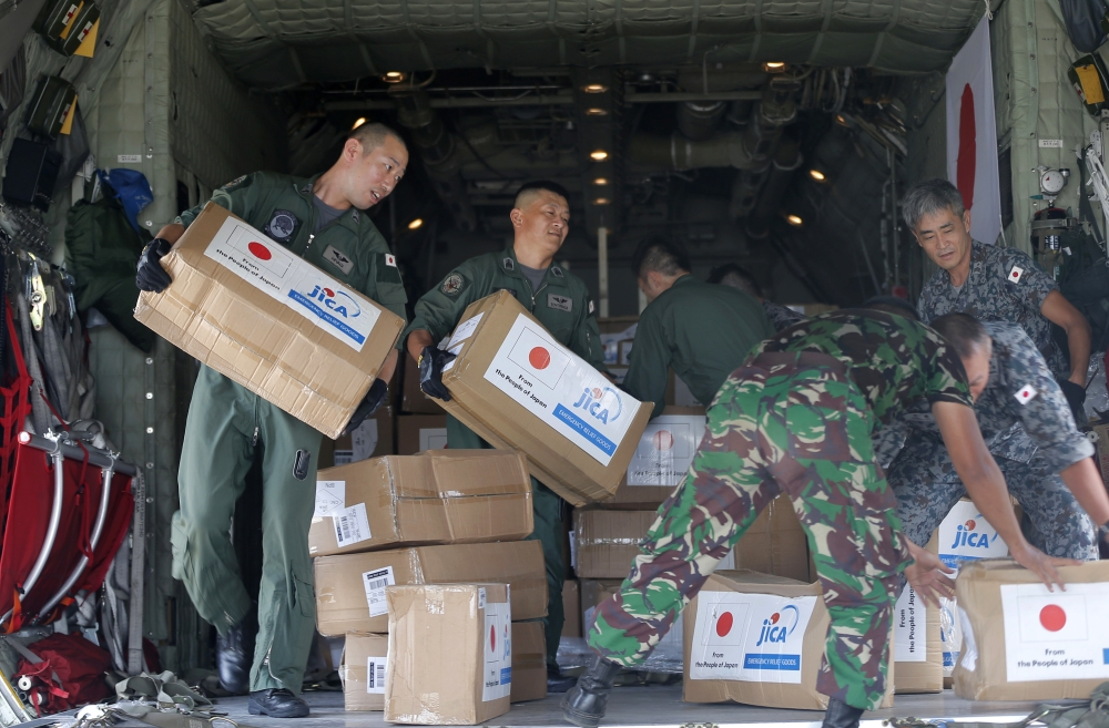 INDONESIA. Indonesian and Japan military personnel unload relief aid from a Japan Air Force cargo plane at the Mutiara Sis Al-Jufri airport in Palu, Central Sulawesi, Indonesia, Saturday, Oct. 6, 2018. As the sun slipped behind the mountains and a gentle breeze blew onshore, hundreds of people gathered on an Indonesian beach Friday to chant a Muslim prayer and remember those they lost one week after a massive earthquake and tsunami ravaged the area, killing more than 1,500 people. (AP)