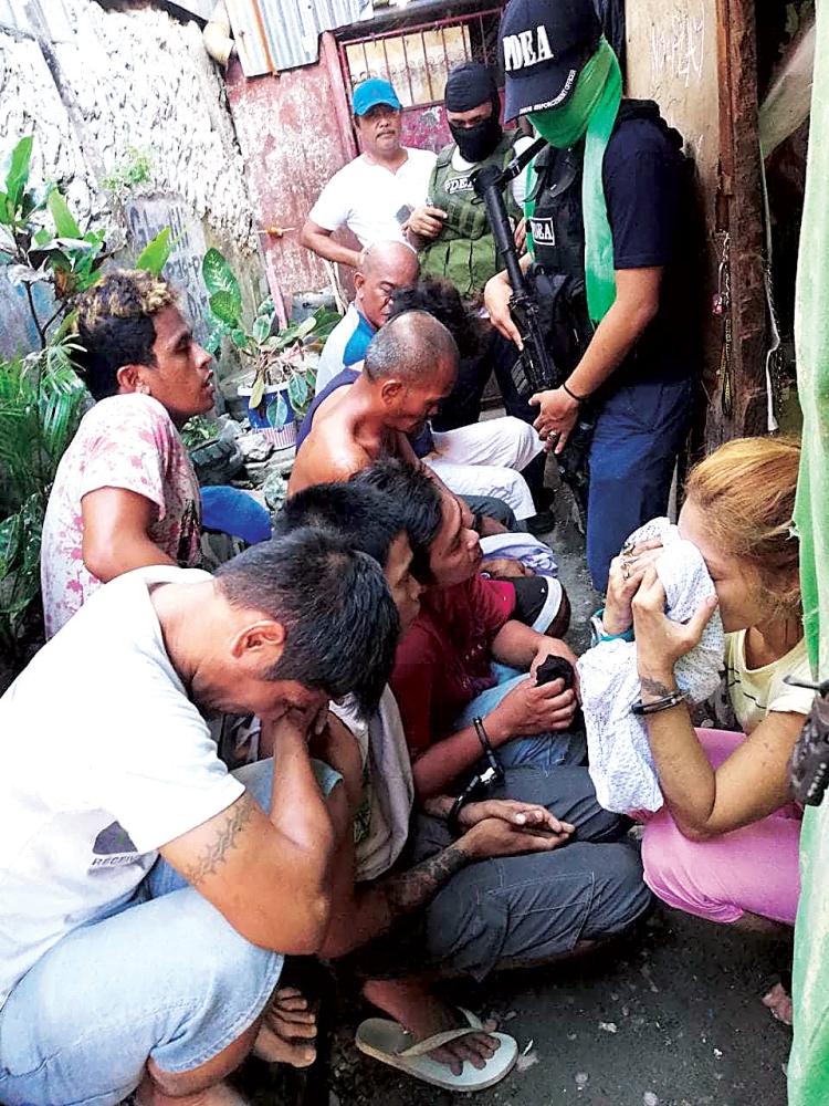 NANAGTUK-ONG: Ang nangasikop gikan sa  usa ka drug den sa  Barangay Duljo Fatima, dakbayan sa Sugbo kagahapon sa hapon ang gipatuk-ong sa awtoridad samtang tulo ka mga ahente sa Philippine Drug Enforcement Agency (PDEA) nagbarog nga nagbantay kanila sa wala pa pangdad-a sa buhatan sa PDEA. (Gikan sa PDEA 7)