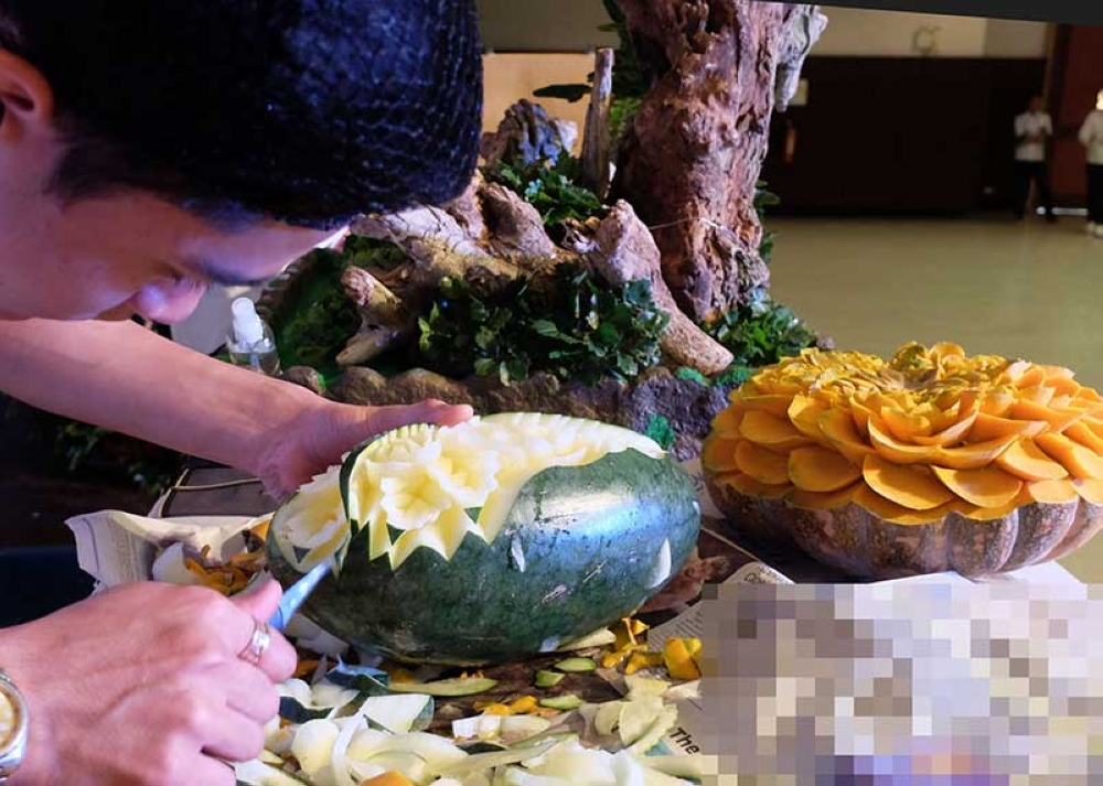 BAGUIO. A food carver carefully sets the details of his masterpiece during the 14th Annual Hotel and Restaurant Tourism Week Skills Competition in Baguio City. (Photo by Dave Leprozo Jr.)