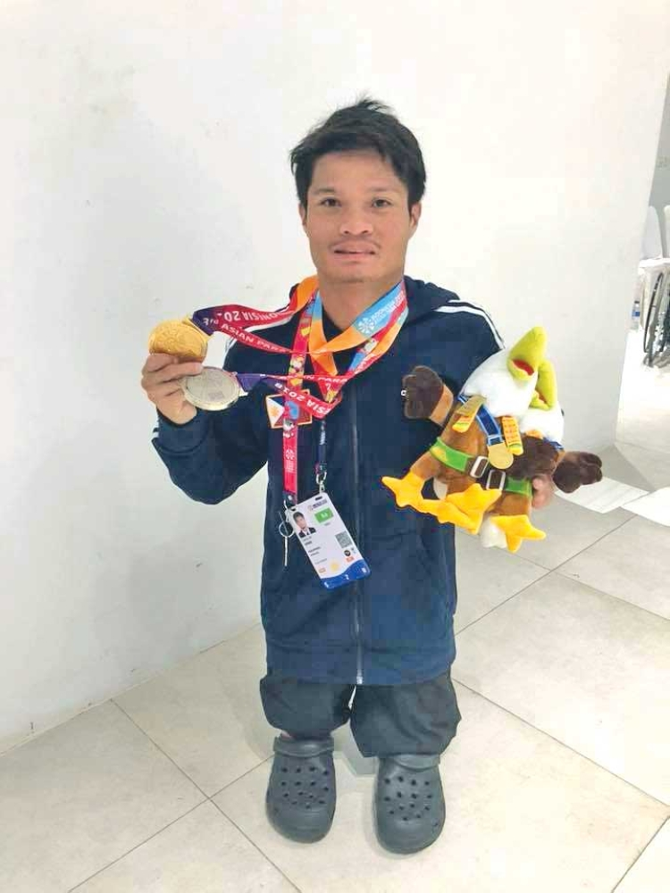STANDING PROUD. Legless Dabawenyo para swimmer Ernie Gawilan shows the gold and silver medals he won in the Asian Para Games 2018 para swimming competition at the Gelora Bung Karno Aquatic Stadium in Jakarta, Indonesia over the weekend. (Majonie Pulumbarit Facebook)
