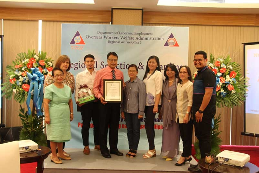111BULACAN. Department of Labor and Employment Assistant Regional Director Geraldine Panlilio and Overseas Workers Welfare Administration (Owwa) Central Luzon officer-in-charge Esperanza Cobarrubias lead the awarding of recognition to Capt. Domingo Cruz and family from Plaridel, Bulacan as Regional Model OFW Family of the Year Award Sea-Based category and Herenio Corpuz and family from Hermosa, Bataan as Regional Model OFW Family of the Year Award Land-Based category. (Photo by OWWA-Central Luzon)