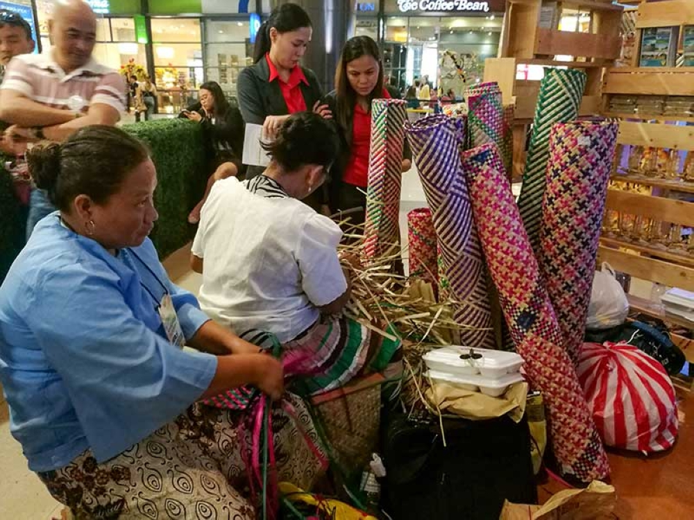HOW IT'S DONE. Banig weavers from Kinatarcan Island off Sta. Fe town show shoppers how they weave dried romblon leaves into a mat. (SunStar photo/Arni Aclao)