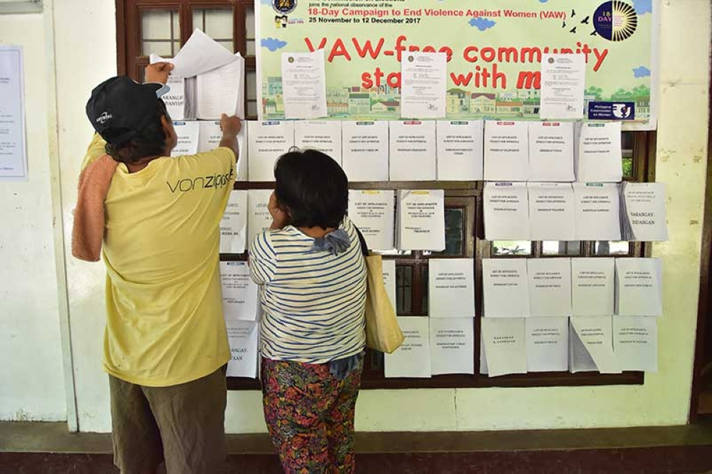 DAVAO. An elderly couple outside the office of the Commission on Elections in Magsaysay Park, Davao City look for their names on the list of the registered voters for the upcoming elections. (Macky Lim)
