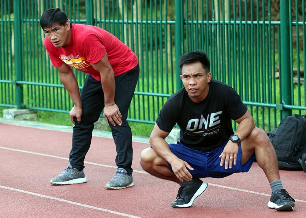 BAGUIO. Former lightweight world champion Eduard Folayang and interim bantamweight champion Kevin Belingon takes a breather during their early morning workout at the Baguio Athletic Bowl. Folayang is set to see action late next month while Belingon will try to unify the bantamweight belt against Bibiano Fernandes on November 9 in the co-main event of One Championship's Heart of the Lion in Singapore. (Photo by Jean Nicole Cortes)