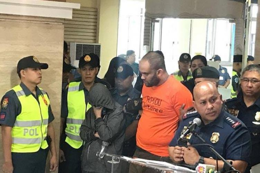MANILA. Egyptian national Fehmi Lassoued (in orange shirt) was presented to media after his arrest in February 2018. (SunStar File)