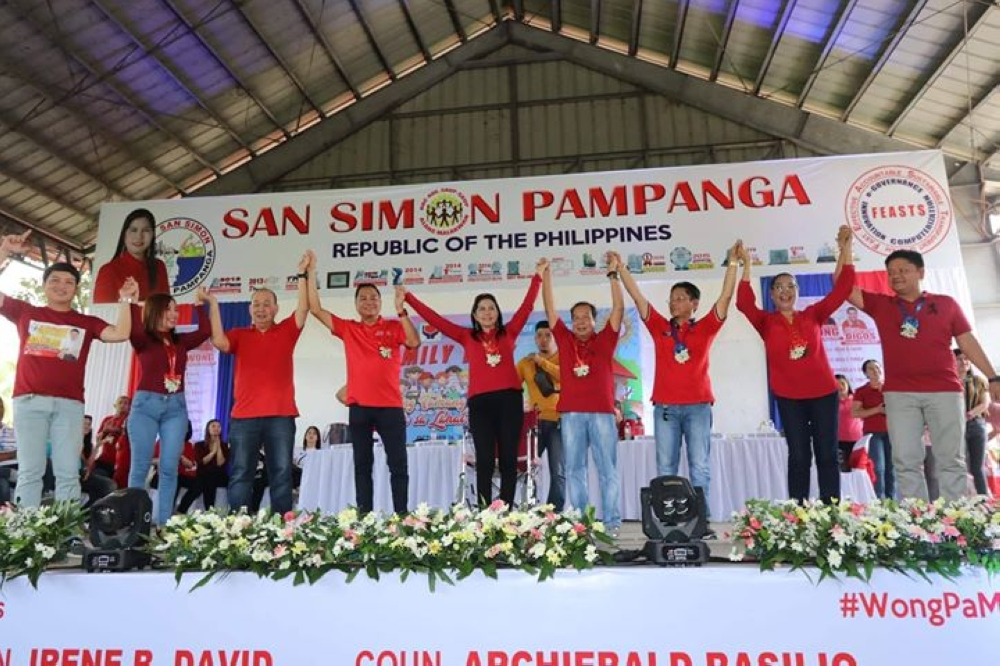 "PAMPANGA. Comebacking San Simon Mayor Rodrigo ""Digos"" Canlas and vice-mayor candidate Mayor Leonora Wong raise the hands of their fellow candidates: re-electionist councilors Irene David, Beda Pineda, Archie Basilio, Glenn Yabut, Crisanta Macapagal, aspiring councilors barangay chairmen Ruben Alfaro and Rogelio Salvador Jr., after filing their COCs on Tuesday, October 16. (Photo by Chris Navarro)"