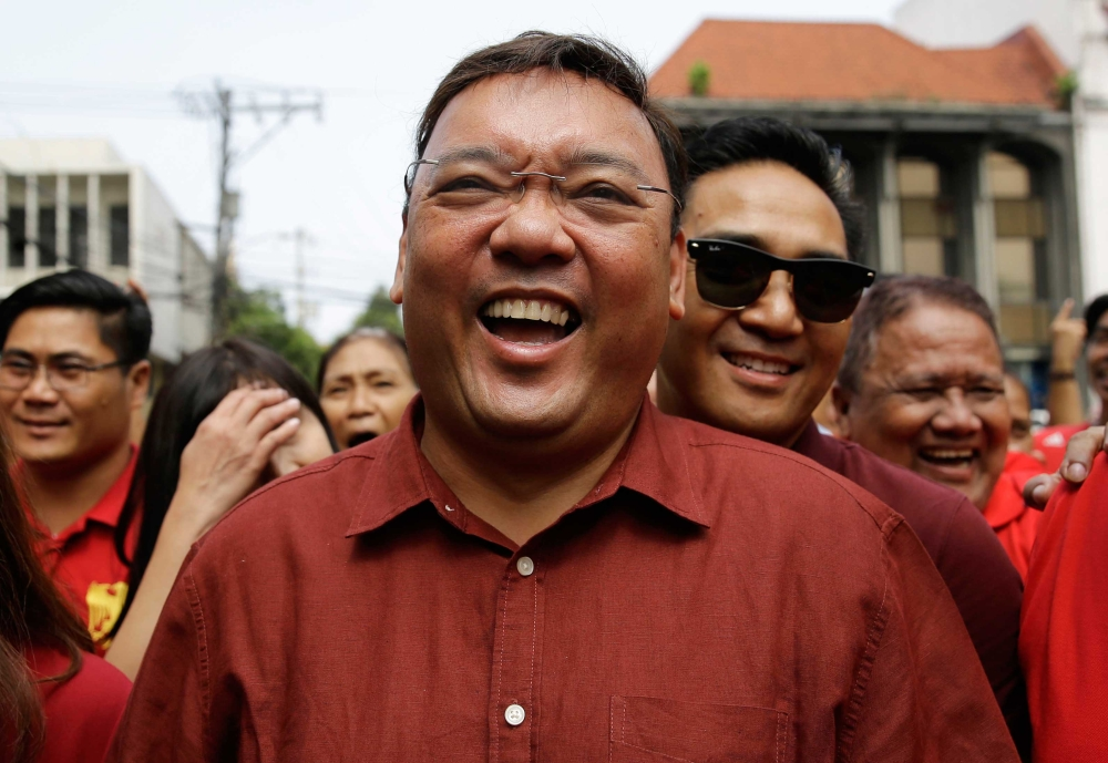 MANILA. Former Presidential Spokesperson Harry Roque laughs as he walks with supporters towards the Commission on Elections to file his candidacy for senator in Manila, Philippines on Wednesday, Oct. 17, 2018. (AP)
