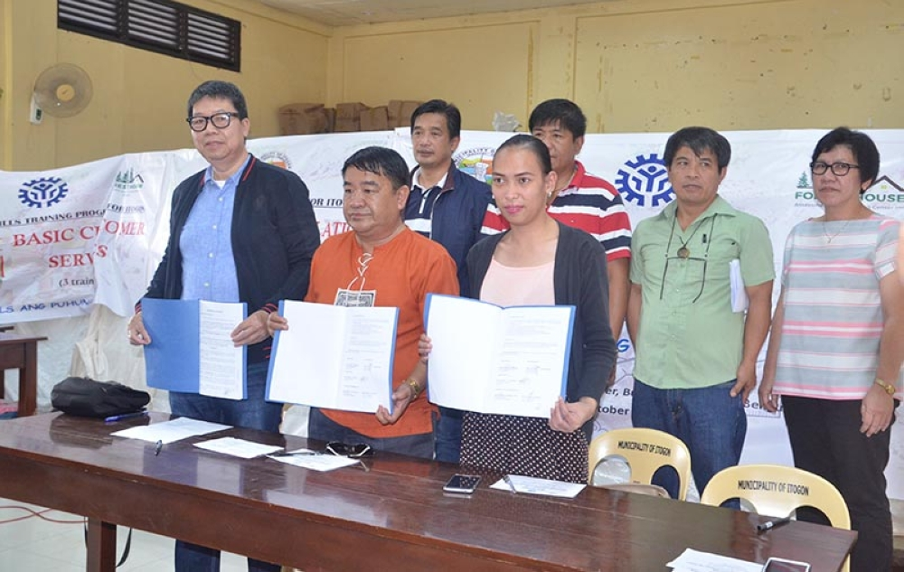 FREE SKILLS TRAINING. TESDA-Cordillera Regional Director Manuel Wong, Itogon Benguet Mayor Victorio Palangdan (middle) and a representative of Forest House Assessment and Training Center Inc. owner Raquel Verzosa left-right) show the Memorandum of Agreement for TESDA's Special Skills Training Program for Typhoon Ompong-affected residents of Itogon. At the back row are Tesda Baguio-Benguet Director David Bungallon (left) and other Itogon officials. (Carlito Dar)