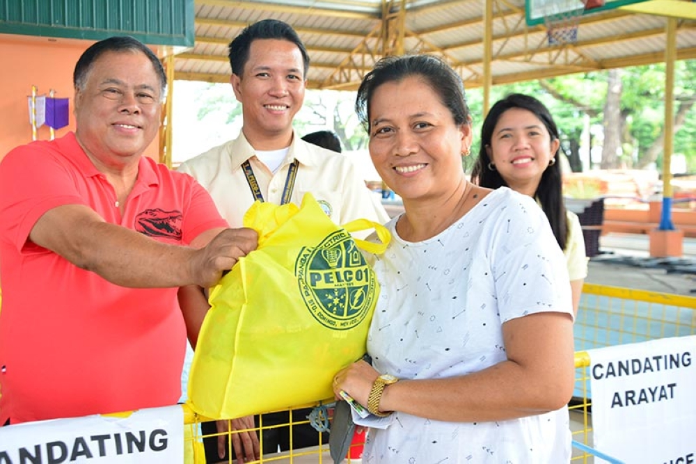 PAMPANGA. Pelco I Arayat Director Rodrigo Santiago smiles with a happy electric cooperative consumer after the latter received a bag of goodsies. (Contributed photo)