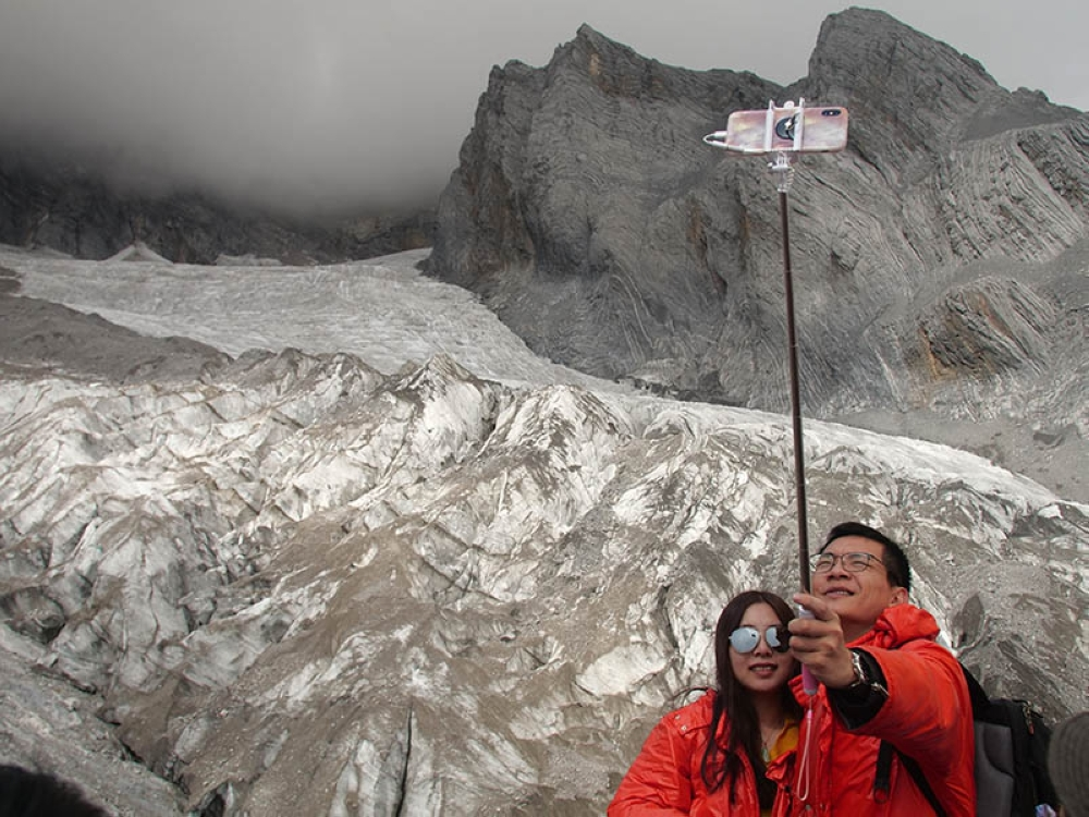 CHINA. This September 22, 2018 photo shows tourists posing for a selfie before the Baishui Glacier No. 1 atop of the Jade Dragon Snow Mountain in the southern province of Yunnan in China. Scientists say the glacier is one of the fastest melting glaciers in the world due to climate change and its relative proximity to the Equator. It has lost 60 percent of its mass and shrunk 250 meters since 1982. (AP Photo)
