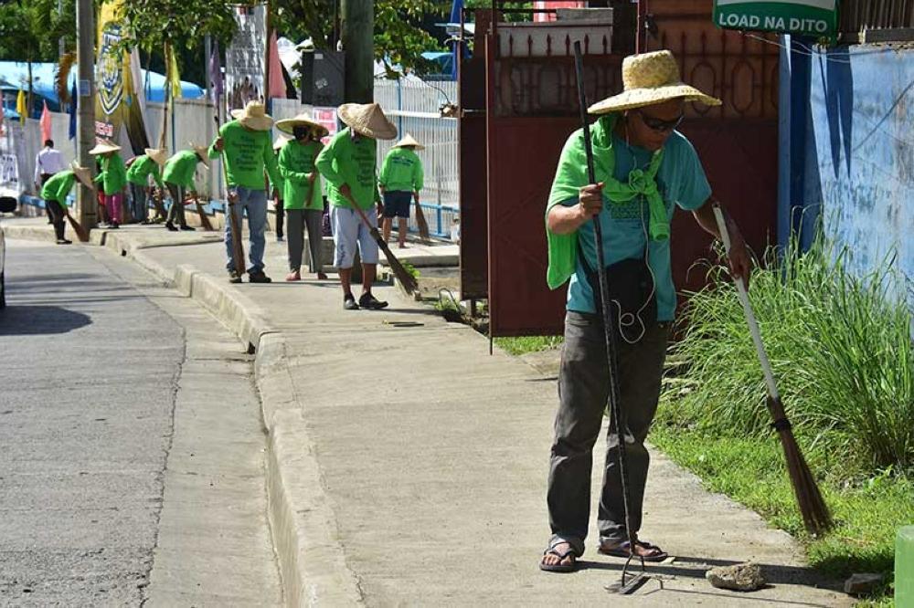 DAVAO. Pipila ka mga molupyo gilimpyohan ang sidewalk sa dalang Lopez Jaena, Barangay 8-A, Davao City kagahapon sa buntag ubos sa programa sa Department of Labor and Employment nga cash-for-work program. (Macky Lim)