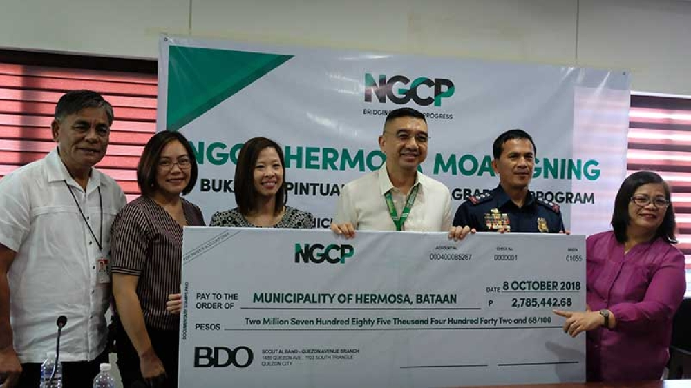 "PAMPANGA. Hermosa Mayor Antonio Joseph Inton (3rd, R) received the P2.7 million check from the National Grid Corporation of the Philippines under its ""Bukas na Pintuan Tungo sa Pagbabago"" program which provides assistance to drug reformists in the town. (Photo by PIA)"