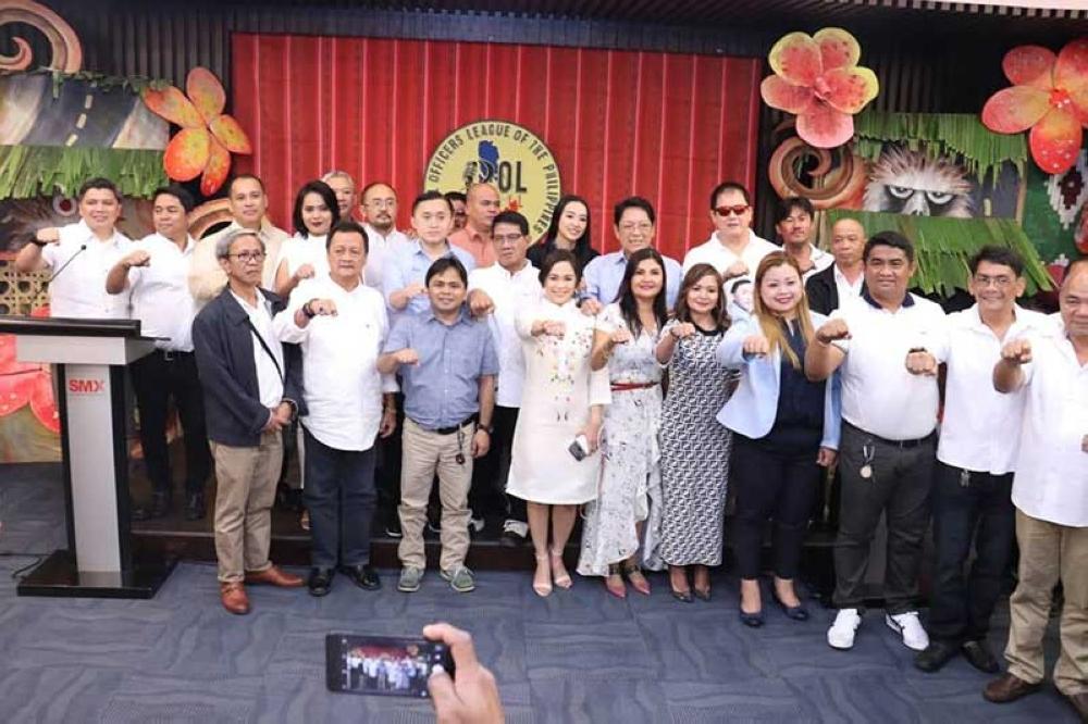 """DAVAO. Mga sakop sa Political Officer League of the Philippines (POLPhil) nagpahulagway uban sila senatorial candidate Bong Go, Sec. Bebot Bello, ug kanhi PCOO Asec. Margaux """"Mocha"""" Uson human sa gipahigayong oath-taking ceremony Lunes sa hapon sa SMX convention, SM Lanang Premier, Davao City. (Roland Jumawan)"""