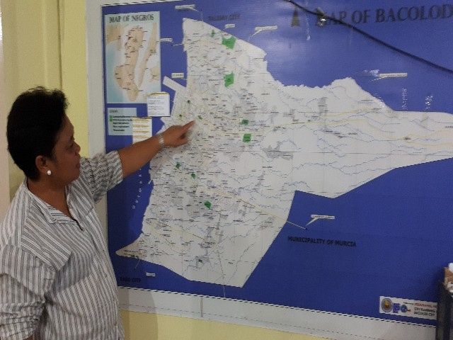 BACOLOD. City Veterinarian Agueda Trinidad DeLa Torre shows the areas covered by the rabies vaccination program of Bacolod City. (Photo courtesy of the Philippine Information Agency)