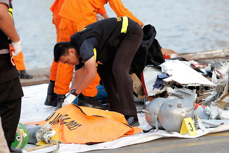 INDONESIA. A member of police forensic team examines the remains recovered from the area where a Lion Air passenger jet crashed, at Tanjung Priok Port in Jakarta, Indonesia Monday, October 29, 2018. (AP)