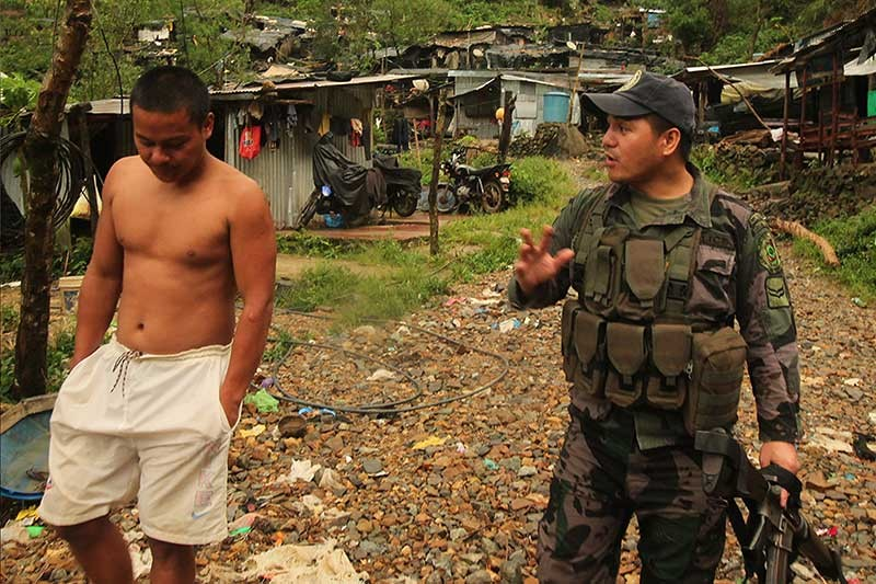 BENGUET. In Itogon, police try to convince a miner in Tuding to evacuate his shanty as Typhoon Rosita approached Benguet. The Department of Environment and Natural Resources (DENR) has enforced an order to stop all illegal mining activities in the Cordilleras. (Photo by Jean Nicole Cortes)